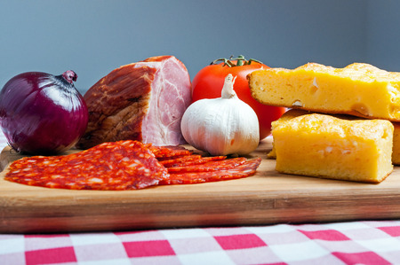 Cornbread with cheese, vegetables and meat on cutting board Stock Photo