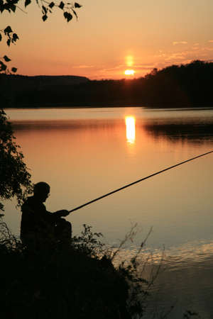 fishing lake: Fisherman catches fish  He was in the background the lake with  Silhouette