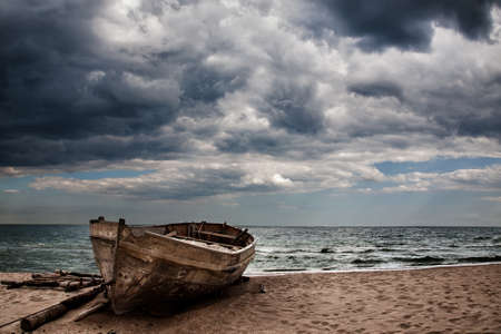 An old fishing boat on the beach  Stormy skies  photo