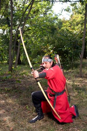 medieval dress: El hombre en traje medieval tiene como objetivo un arco.