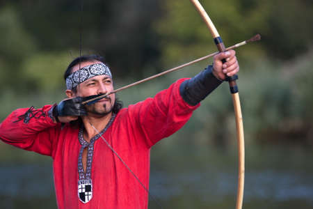 medieval dress: Man in medieval dress aims a bow. Stock Photo