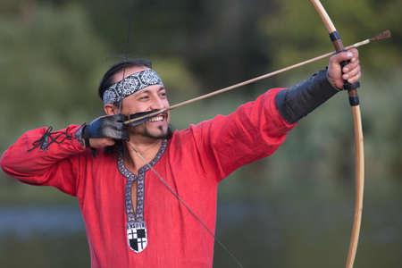 vestido medieval: El hombre en traje medieval tiene como objetivo un arco.