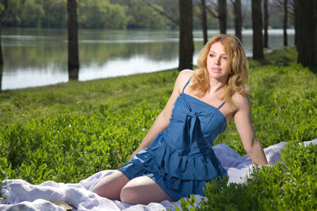 coverlet: blonde girl lying in the park with tablet on the red coverlet. summer