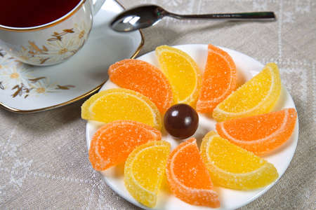Marmalade on a saucer and a cup of tea. One candy. Stock Photo