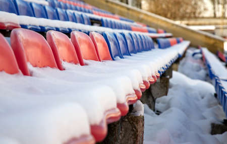 fandom: Partially snow covered red and blue seats in the stadium.
