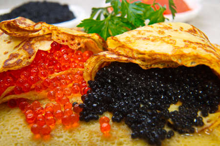 blini: Pancakes with red and black caviar. Caviar wrapped in pancakes. Stock Photo