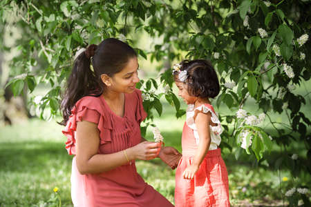 A happy woman in red dress with two years old girl in spring park Фото со стока