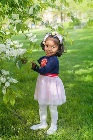 A two years old girl at a blooming branch of bird cherry tree Фото со стока