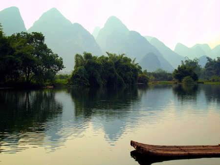 karst: a raft and background mountian on Yu Long river in Yangshou, China Stock Photo