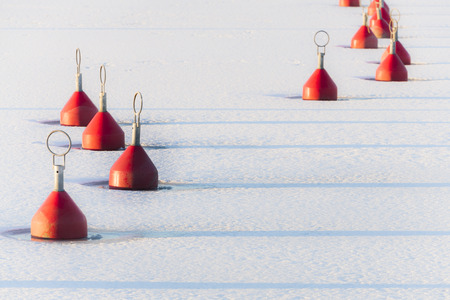 buoys: Red buoys in a Finnish haven in February