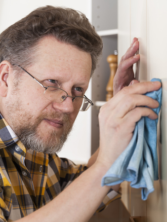 one mid adult man only: 50+ man doing household chores at home