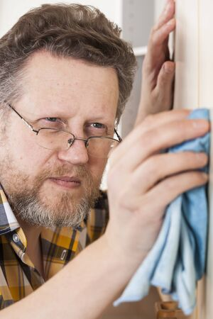 only one mid adult male: 50+ man doing household chores at home