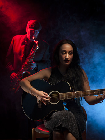 saxophonist: Young beautiful guitarist and an older saxophonist