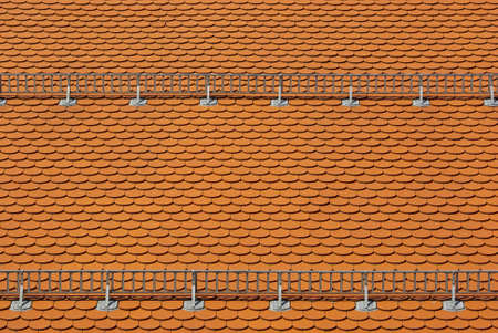 A roof covered with red tiles and snow guards attached.