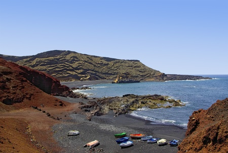 View of fishing boats and the coast line by the fishing village of El Golfo on the Spanish Canary isle of Lanzarote.