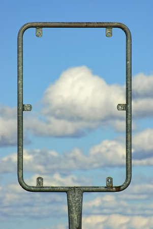 Een metaal gevatte wegwijzer die als houder van een uithangbord op een bewolkte blauwe hemel.