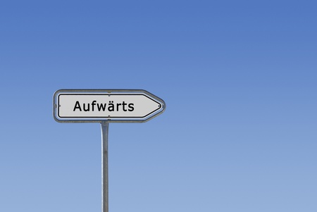 Ein Schild, Hinweisschild und Wegweiser, auf dem Aufwärts steht, freigestellt vor blauem Himmel Farbverlauf.