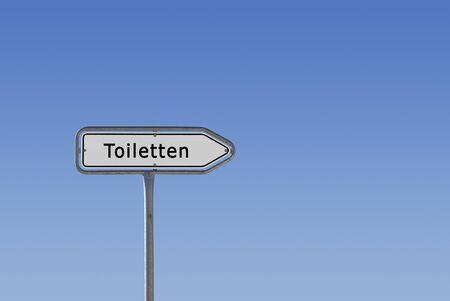 Ein Schild, Hinweisschild und Wegweiser, auf dem Toiletten steht, freigestellt vor blauem Himmel Farbverlauf. Stock Photo