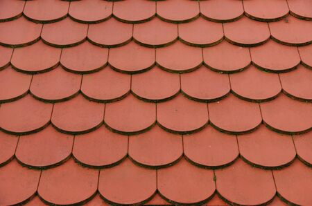 Rode dakpannen gerangschikt als schubben een uitstekende achtergrond Stockfoto
