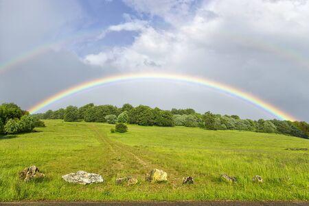 Dubbele regenboog over heuvelachtig grasland na een onweersbui regen