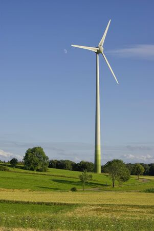 Wind turbine in rural idyllic landscape under  blue sky and moon
