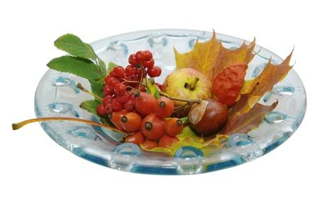 Seizoensgebonden decoratie van vruchten en bladeren in een opengewerkte glazen schaal Stockfoto