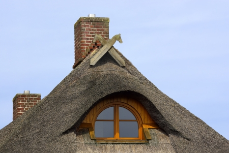 Reed-covered roof of a typical Northern German residential house, with single window and gable decoration