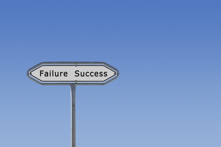 A signpost poiting into two directions, Success and Failure