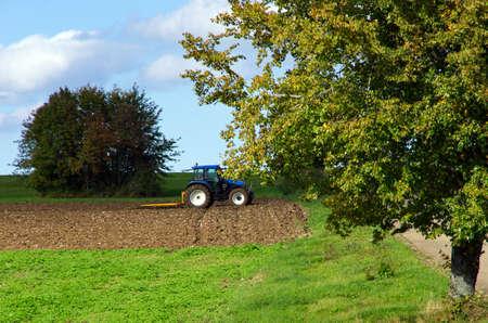 Landelijke omgeving met tractor en eg in de vroege herfst