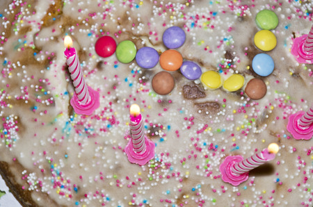 glazing: Chocolate lentils make a seven on a birthday cake with glazing, checkered sugar sprinkles and candles. Stock Photo