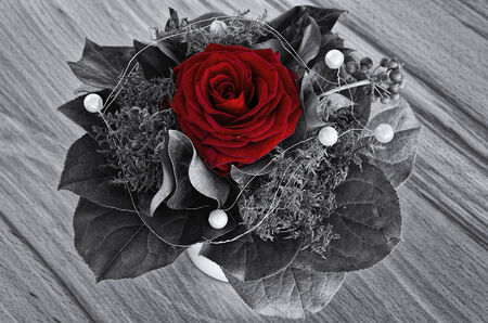 Single rose with greens and deco beads in a bouquet, in a vase, on a wooden ground, in black and white.