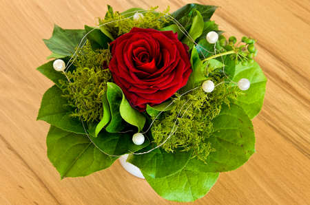Single rose with greens and deco beads in a bouquet, in a vase, on a wooden ground.