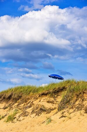 Beach and dune and beach grass and sunshade. Stock Photo