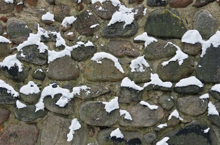 Wall of cobblestones covered with snow.