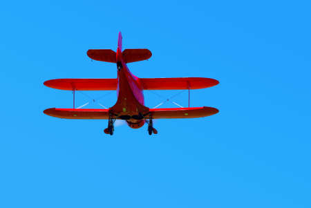 Red vintage biplane in the air from behind. Stock Photo