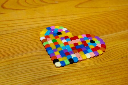 Heart shape of colorful fuse beads on a wooden surface.