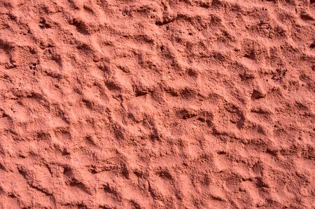 Detail of a brown-red-orange colored exterior plaster with rough-textured pattern.