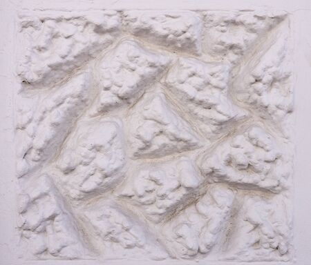 cartouche: Rough-textured pattern of white colored exterior plaster.