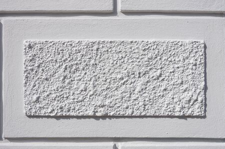 Detail of an exterior facade with rectangular plastered structure.