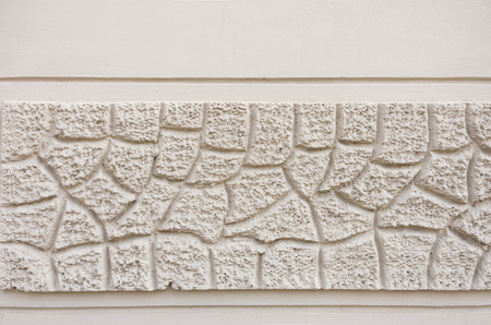 Detail of an exterior facade with a frieze of rough textured and grooved beige plaster.