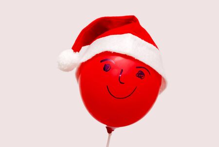 Red balloon with friendly face and Christmas bonnet on isolated against a cream background.