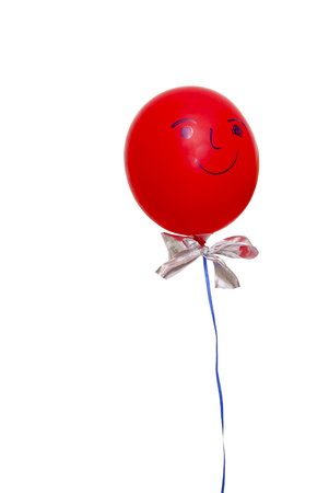 Red balloon with face, bow and ribbon floats in front of a white background.