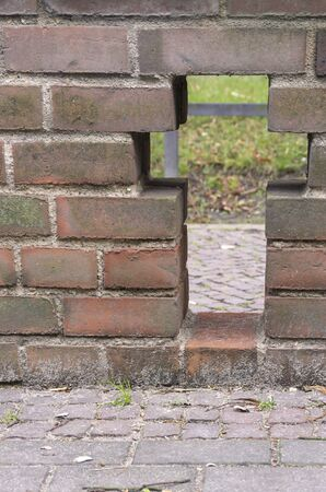 Cross-shaped perforation in a brick wall. Archivio Fotografico