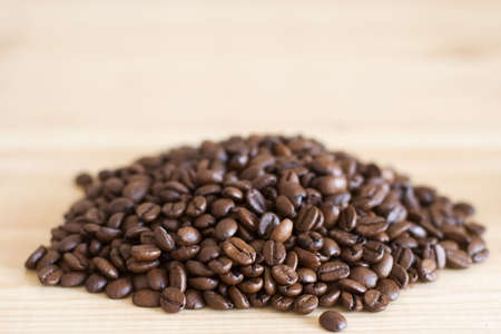 heaped: heaped coffee beans on wooden surface