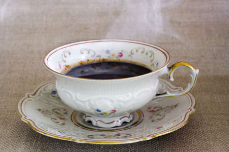 Antique cup with hot steaming coffee on the sackcloth  Stock Photo