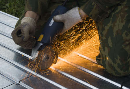 metal cutting sparks  (Man in khaki Working under Metal) Stock Photo - 1133934
