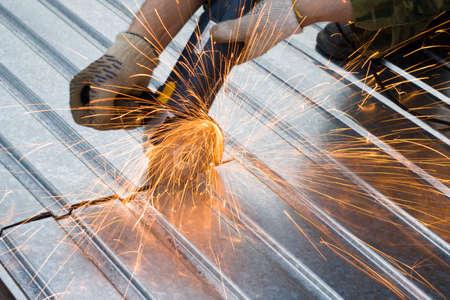 metal cutting sparks  (Man in khaki Working under Metal)