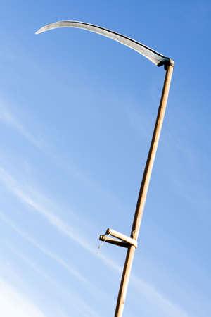 stab: raised for stab sharpen scythe on sky background