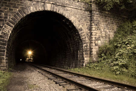 From dark to light. Old (1902-1904), long (0.78 km) and straight railroad tunnel of the Circum-Baikal Road, the historical part of Trans-Siberian railway, near Lake Baikal, Russia. In total, part of the railroad from source of Angara river to the south en photo