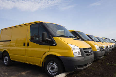 Row of yellow blank delivery vans or trucks photo